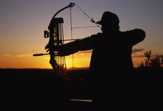 Bowhunter at Full Draw. A bowhunter at full draw silhouetted in the sunrise Stock Photography