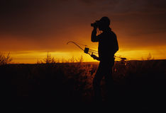 Bowhunter Glassing. A bowhunter glassing silhouetted in the sunrise Stock Photo