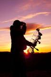 Bowhunter Glassing dans le coucher du soleil Images stock