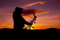 Bowhunter Glassing in Sunset. A bowhunter glassing while silhouetted in the sunset Royalty Free Stock Photography
