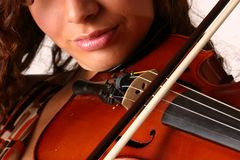 Bowing a Violin. Close up view of a girl playing a violin showing detail of the bow and the strings Royalty Free Stock Photos