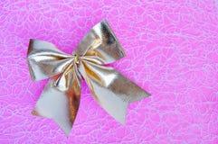 Bowknot d'or sur un fond rose Photo libre de droits