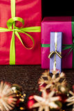 Bowknots, presents, stars and twinkles. Focus on three presents wrapped in blue, magenta and crimson in the background. The sharp outlines of the golden bowknot Stock Images