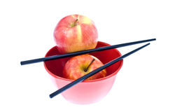 Bowl with 2 apples and 2 chinese sticks Stock Image