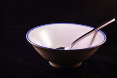 Bowl. And empty bowl with spoon symbolizing hunger, isoloated on black Stock Images