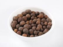 Bowl of allspice berries. On white background royalty free stock image