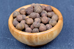 Bowl with allspice on slate. Closeup stock images