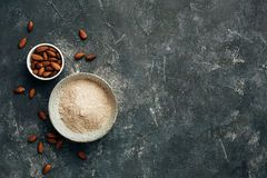 Bowl of almond flour and bowl of almonds from top view, copy space. Stock Images