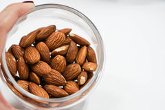 Bowl of almonds. Close up a transparent bowl of almonds in hand Stock Photography