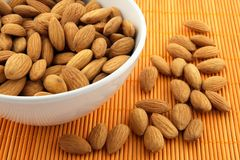 Bowl of almonds on rattan mat Royalty Free Stock Image