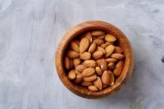 Bowl of almonds on white textured background, top view, close-up, selective focus. Wooden bowl of almonds on white textured background, top view, close-up royalty free stock image