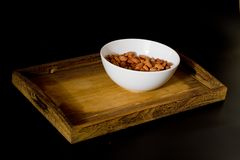 Bowl with almonds on wooden tray Royalty Free Stock Photo