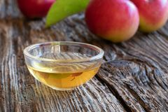 A bowl of apple cider vinegar with fresh apples stock photos
