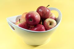 A Bowl of Apples. A white bowl of shiny apples against a pale yellow background Stock Photography