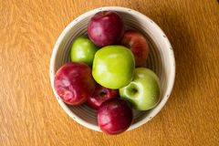 Bowl of Apples from above. Fresh picked ripe red and green apples in a white bowl over a wooden background from above Stock Image