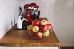 Bowl with apples on kitchen table. Bowl with red apples on wooden table, in white kitchen Stock Images