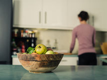 Bowl of apples in kitchen with woman in background Stock Images