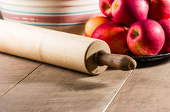 Bowl of apples with a rolling pin Royalty Free Stock Images