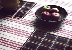 Bowl with apples on a wood with striped tablecloth Royalty Free Stock Photography