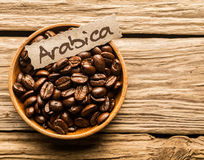 Bowl of Arabica coffee beans. Bowl full of Arabica coffee beans over an old wooden table Stock Photos
