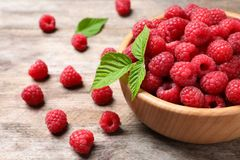 Bowl with aromatic raspberries on wooden table. Bowl with ripe aromatic raspberries on wooden table Stock Image