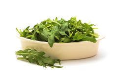 Bowl of arugula on white background Royalty Free Stock Image