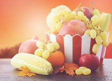 Bowl of Autumn fruit and vegetables with sunset background. Stock Images