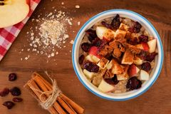 Bowl of autumn inspired oatmeal with apples and cranberries. Overhead scene on a wood background Royalty Free Stock Images