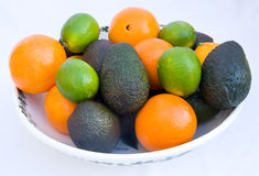 Bowl of avacado pears, oranges and limes. Stock Images