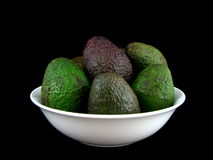 Bowl of Avocadoes. Avocadoes in white bowl isolated on black background Stock Image