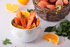 Bowl with baked carrots, coriander and orange. Carrots baked with orange and coriander in ceramic bowl Stock Images