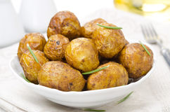 Bowl of baked new potatoes with spices and rosemary Stock Photography
