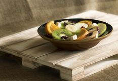 A bowl with banana, apple, kiwi, orange and cranberries royalty free stock photography