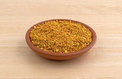 Bowl of bee pollen granules on a wood table Royalty Free Stock Images