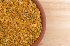 Bowl of bee pollen granules on a wood table Stock Image