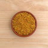 Bowl of bee pollen granules on a wood table Royalty Free Stock Photography