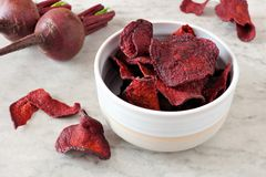 Bowl of beet chips over white marble Royalty Free Stock Images