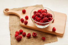 The bowl and berries. Frozen raspberries in a glass bowl. Berries on a cutting board . Prepare dessert Royalty Free Stock Images