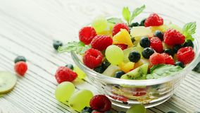 Bowl with berries and fruit. Glass bowl filled with sweet assortment of fruit and berries garnished with mint leaves and served on wood table stock footage