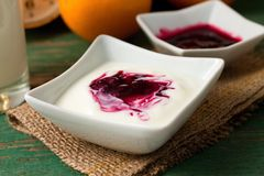 Bowl with berry fruit in white yogurt placed on jute cloth Stock Photos