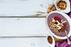 Bowl of berry smoothie. Diet berry smoothie bowl topped with berries, shredded coconut, seeds and oats on white wooden background, top view, copy space Stock Photography