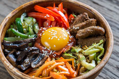 Bowl of bibimbap on the wooden table Royalty Free Stock Photos