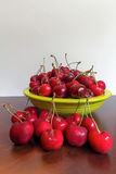 Bowl of Bing Cherries. Bing Cherries in a green lime green bowl on a wood table Stock Images