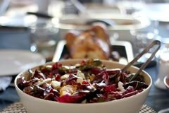 Bittersweet Salad. Bowl of bittersweet salad with oranrges, radicchio, ricotta cheese and pomegranate seeds. Table served for family and friends. Selective focus stock photos
