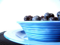 Bowl of black and blue. Mixed blueberries and blackberries in a bowl on a plate on a black placemat stock image