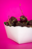 Bowl of black cherries on bright pink background. A still-life of some fruit on a pink background Royalty Free Stock Photos
