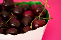Bowl of black cherries on bright pink background. A still-life of some fruit on a pink background Stock Image