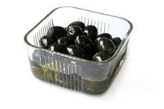 Bowl of black olives. Fresh European black olives with olive oil Stock Image