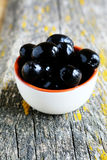 Bowl with black olives on rustic wooden table Stock Image