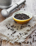 Bowl of black pepper on wooden table Royalty Free Stock Images